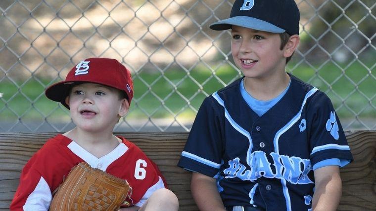 野球のユニフォームを着てベンチに座る兄弟
