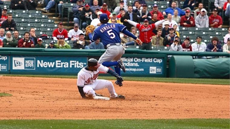 ベースにスライディングする選手とボールをジャンピングキャッチする選手