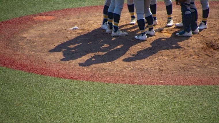 マウンドとそこに集まる選手たちの足