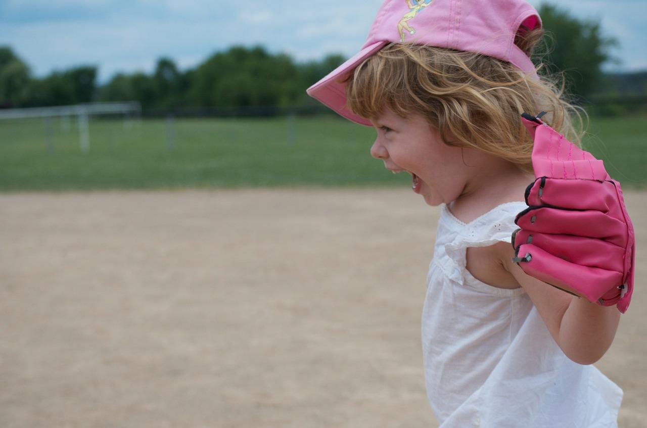 小さな女の子がグローブをして喜んでいる