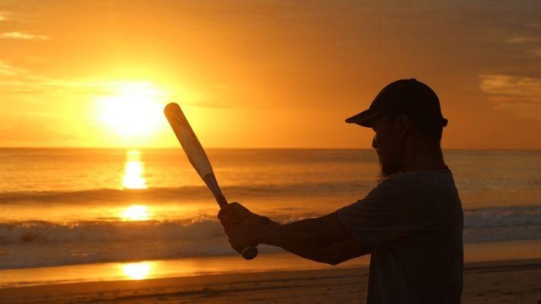 海辺で夕日に向かって素振りする男性